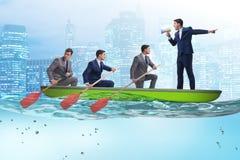 L'équipe d'hommes d'affaires dans le concept de travail d'équipe avec le bateau Photo stock