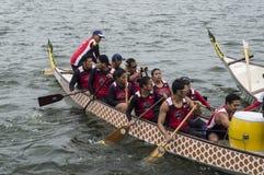 L'équipe de concurrence de personnes s'embarquent sur le bateau de rangée indigène de sports pendant le Dragon Cup Competition photographie stock libre de droits