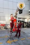 L'équipe de Ferrari le jeudi dispose l'équipement pour fonctionner le duri Image stock