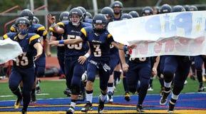 L'équipe de football américaine de lycée entre dans la zone Images stock