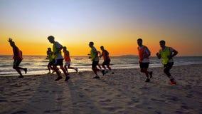 L'équipe de football courant au coucher du soleil sur la plage vide Photographie stock