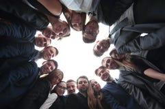 L'équipe de grande entreprise forme un cercle et regarde l'appareil-photo Photographie stock libre de droits