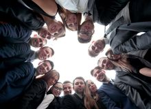L'équipe de grande entreprise forme un cercle et regarde l'appareil-photo Photos libres de droits