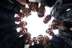 L'équipe de grande entreprise forme un cercle et regarde l'appareil-photo Photos stock