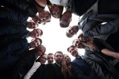 L'équipe de grande entreprise forme un cercle et regarde l'appareil-photo Images libres de droits