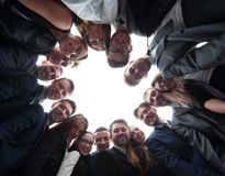 L'équipe de grande entreprise forme un cercle et regarde l'appareil-photo Photographie stock