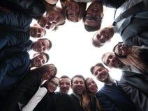 L'équipe de grande entreprise forme un cercle et regarde l'appareil-photo Photo stock