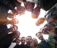 L'équipe de grande entreprise forme un cercle et regarde le camer Images stock