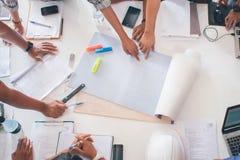 L'équipe de personnes d'architectes dans le groupe sur le site de construciton vérifient le déroulement des opérations de documen Image stock