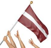 L'équipe de peuples remet soulever la Lettonie drapeau national Image libre de droits