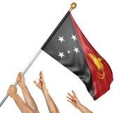 L'équipe de peuples remet soulever la Papouasie-Nouvelle-Guinée drapeau national Images stock
