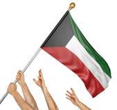 L'équipe de peuples remet soulever le Kowéit drapeau national Photographie stock libre de droits