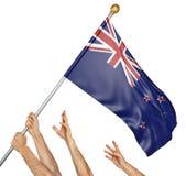 L'équipe de peuples remet soulever le Nouvelle-Zélande drapeau national Photographie stock libre de droits