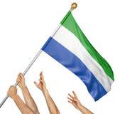 L'équipe de peuples remet soulever le Sierra Leone drapeau national Images stock