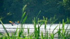 L'équipe de sports appareillent le canoë emballant sur la rivière sauvage de l'eau par des roseaux banque de vidéos