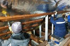 L'équipe des maîtres installe le toit de la maison, et visse en particulier les vis dans les conseils pour fixer le film d'alum photographie stock libre de droits
