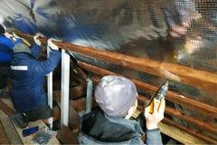 L'équipe des maîtres installe le toit de la maison, et visse en particulier les vis dans les conseils pour fixer le film d'alum photo libre de droits