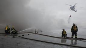 L'équipe des pompiers combattant avec l'incendie photo stock