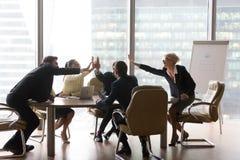 L'équipe exécutive diverse d'affaires donnent hauts cinq dans le bureau moderne images libres de droits