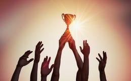 L'équipe gagnante tient le trophée dans des mains Silhouettes de beaucoup de mains dans le coucher du soleil photos stock