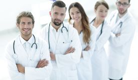 L'équipe médicale se tenant avec des bras a croisé sur un fond blanc photographie stock