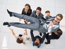 L'équipe triomphante d'affaires secoue leur chef Photographie stock libre de droits