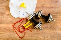 L'équipement de sport, corde, forme physique, boule, sports, serviette, espadrilles, plancher en bois, chaussures de course, folâ Image stock