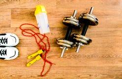 L'équipement de sport, corde, forme physique, boule, sports, serviette, espadrilles, plancher en bois, chaussures de course, folâ Image libre de droits