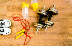 L'équipement de sport, corde, forme physique, boule, sports, serviette, espadrilles, plancher en bois, chaussures de course, folâ Photos stock