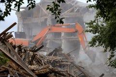 L'équipement travaille au démontage du bâtiment, de la poussière et des débris image libre de droits