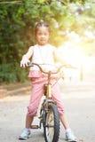 L'équitation asiatique d'enfant fait du vélo extérieur photographie stock libre de droits