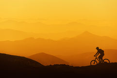 L'équitation de cycliste sur la montagne silhouette le fond Photos stock