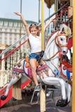 L'équitation de fille sur un joyeux vont rond Petite fille jouant sur le carrousel, l'amusement d'été, l'enfance heureux et le co Photos libres de droits