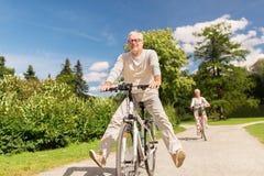 L'équitation supérieure heureuse de couples va à vélo au parc d'été images libres de droits