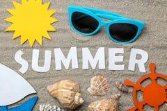 L'été de mot des lettres blanches de papier et été et accessoires de mer sur le sable de mer ?t? Vacances Relaxation Vue sup?rieu photos libres de droits