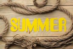 L'été de mot fait en lettres et corde jaunes de papier de mer sur un fond en bois naturel ?t? Vacances Relaxation Vue sup?rieure images stock