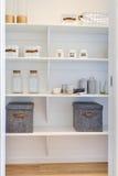 L'étagère en bois blanche a inclus des boîtes et des tasses en métal avec des bouteilles Photographie stock libre de droits