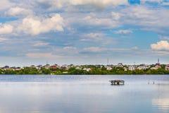L'étendue bleue du lac et du village près d'a photographie stock