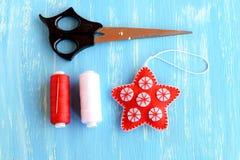 L'étoile rouge de Noël diy, le rouge et le blanc filètent, l'aiguille, ciseaux sur le fond en bois bleu Ornement fabriqué à la ma Photos libres de droits