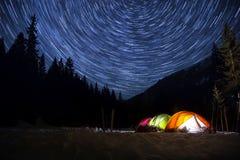 L'étoile traîne dans le ciel nocturne au-dessus de la tente temps-faute Photos stock