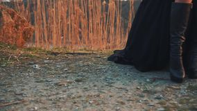L'étranger mystérieux dans de hautes bottes en cuir noires et une robe volante légère foncée se tient au sol dans la zone montagn banque de vidéos
