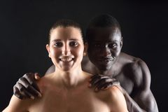 L'étreinte d'un couple interracial sur le noir Photographie stock