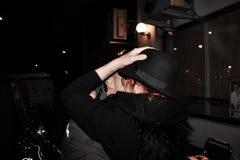 l'étreinte d'un couple le soir, la femme tient son chapeau qu'elle était perte due à la chaleur photographie stock libre de droits