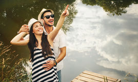L'étreinte des couples romantiques heureux sur le pilier explorent le monde de soit photographie stock libre de droits