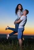 L'étreinte romantique de couples au coucher du soleil, ami soulèvent l'amie, le beau paysage et le ciel jaune lumineux, conce de  Images libres de droits