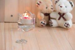 L'étreinte soutient dans l'amour, se repose près de la bague de fiançailles et du chandelier Photos stock