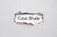 L'étude de cas de mot apparaissant derrière le papier déchiré Photographie stock