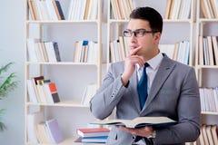 L'étude travaillante d'étudiant de droit des affaires dans la bibliothèque photographie stock