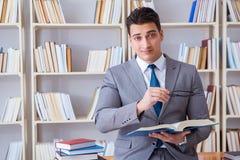L'étude travaillante d'étudiant de droit des affaires dans la bibliothèque photo stock
