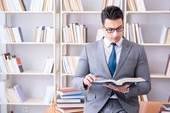 L'étude travaillante d'étudiant de droit des affaires dans la bibliothèque photos stock